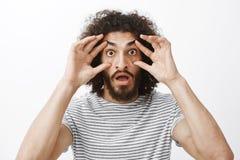 方式,不可能相信我的视域 Shocked使有卷发和胡子的滑稽的人惊奇,舒展有手指的眼皮和 免版税库存照片
