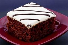 方形的切片在绯红色板材的红色天鹅绒蛋糕 库存照片