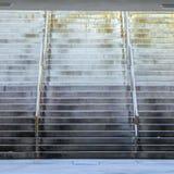 方形的有发光的金属扶手栏杆的框架宽阶梯步级在大厦下 免版税图库摄影