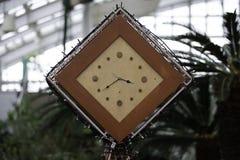 方形的木时钟有庭院背景 免版税库存图片
