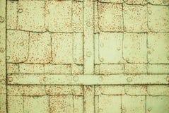 从方形的板料的黄绿铁门与铆钉和板条,在棕色铁锈斑点 免版税库存照片
