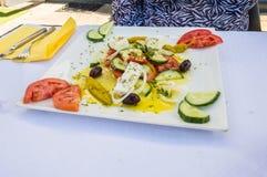 方形的板材被做希腊沙拉用希脂乳,蕃茄,橄榄, 免版税图库摄影