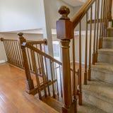 方形的框架与棕色扶手栏杆的覆盖着的楼梯在有发光的木地板的一个房子里面 库存图片