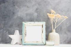 方形的蓝色照片框架嘲笑与花瓶的,在架子的陶瓷装饰干燥米黄植物 斯堪的纳维亚样式 免版税库存图片
