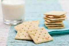 方形的饼干薄脆饼干用在玻璃的新鲜的牛奶 免版税图库摄影