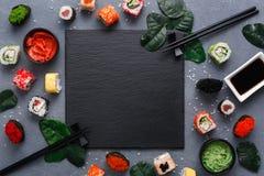 方形的黑板岩板材用在土气灰色backround,拷贝空间的寿司 免版税库存图片