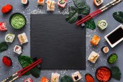 方形的黑板岩板材用在土气灰色backround,拷贝空间的寿司 图库摄影