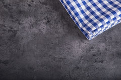 方格的厨房桌布顶视图在花岗岩-混凝土的-石背景 您的文本或产品的自由空间 免版税库存图片