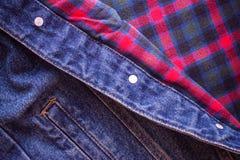 方格的苏格兰织品的样式与创造背景的牛仔裤的 免版税图库摄影