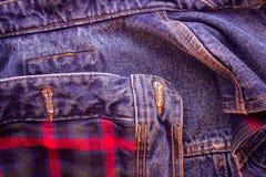 方格的苏格兰织品的样式与创造背景的牛仔裤的 免版税库存照片