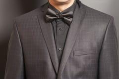 方格的衣服的人和在灰色的黑和黑蝶形领结 免版税库存照片