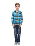 方格的衬衣和牛仔裤的微笑的男孩 免版税库存图片