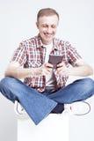 方格的衬衣和牛仔裤的微笑的白种人人聊天在手机的 免版税库存照片