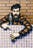 方格的衬衣的人在振动器、砖墙和蓝色桌布背景附近 男服务员忠告概念 有胡子的男服务员 免版税图库摄影