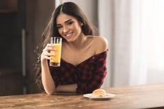 方格的衬衣的性感的女孩吃新月形面包和喝橙汁的 库存图片