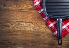 方格的餐巾和聚四氟乙烯平底锅顶视图在木桌上的 免版税库存照片
