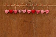 方格花布爱垂悬在木纹理backgr的华伦泰的心脏 免版税图库摄影