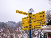 施万高,德国- 2018年2月23日:在著名新天鹅堡城堡的旅游讯息标志在巴法力亚阿尔卑斯 免版税库存图片