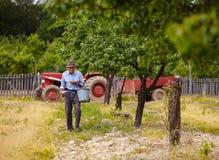 施肥在果树园的老农夫 免版税库存图片