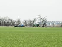 施肥在领域的拖拉机 加油与除草药 免版税图库摄影
