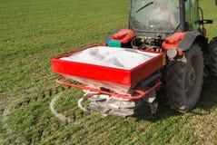施肥在领域的拖拉机 库存照片