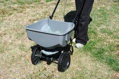 施肥由肥料分布器的草坪 免版税库存图片