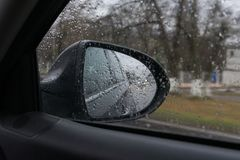 旁边后视镜通过在多雨天气的玻璃 汽车前灯的反射 库存照片