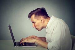 旁边研究计算机的外形年轻人坐在书桌 免版税库存图片