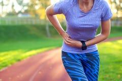 旁边针-妇女赛跑者边抽疯在跑以后 跑步的wo 免版税库存图片