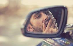 旁边驾驶汽车的镜子视图困疲乏的打呵欠的人在长时间驱动以后 免版税库存照片