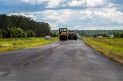 旅团放置沥青的路工作者在路在夏天在特别设备沥青帮助下 免版税库存照片