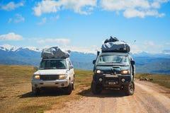 旅客两辆汽车山雪路的环境美化 4x4在山口的吉普汽车,登上峰顶 极端危险冒险 免版税图库摄影