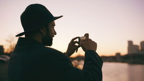 旅客人剪影拍城市地平线的全景照片的在他的智能手机照相机的帽子的在日落