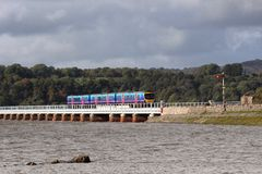 旅客列车在大浪的Arnside高架桥 库存照片