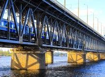 旅客列车沿一座两层的桥梁和一条铁路移动横跨第聂伯河在Dnipro市 库存照片