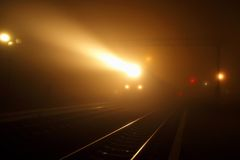旅客列车的聚光灯从有薄雾的夜拔出了 免版税库存照片