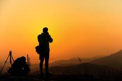 旅客剪影,当他拍摄在山的照片在日出 免版税库存照片