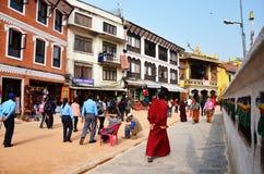 旅客和尼泊尔人民在Boudhanath寺庙街道上去Bodnath Stupa为在加德满都祈祷 免版税库存照片