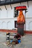 旅客和尼泊尔人民旅行并且祈祷Hanuman雕象 图库摄影