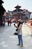 旅客和尼泊尔人民旅行并且采取照片Basantapur Durbar广场 库存图片