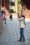 旅客和尼泊尔人民旅行并且采取照片Basantapur Durbar广场 图库摄影