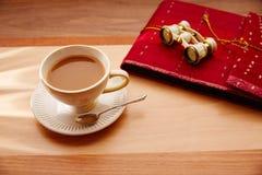 旅客咖啡或牛奶茶与双筒望远镜和笔记本 库存照片