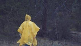 旅客在一件黄色雨衣穿衣 抚养走在与通过背包的艰苦跋涉的后面观点的年轻女性远足者 影视素材