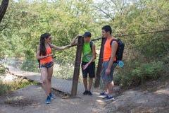 旅客在吊桥旅行去一起迁徙 活跃远足者 Eco旅游业和健康生活方式概念 两youn 库存照片
