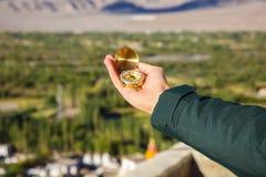年轻旅客在喜马拉雅山山景背景& x28中的看指南针; 在compass& x29的焦点; 库存图片