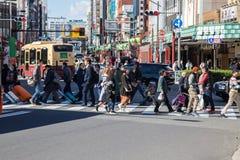 旅客在行人穿越道穿过街道 库存照片