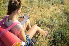旅客在远足保留一本日志 免版税库存图片