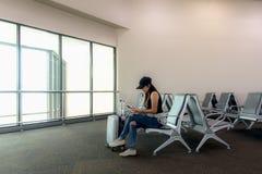 旅客坐在终端大厅里的巧妙的电话的妇女乘客等待她的飞行在机场 免版税库存图片