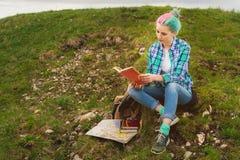 旅客女孩在山在史诗山背景坐草并且读书  概念  免版税库存照片