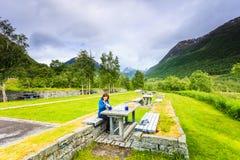 旅客妇女吃在自然的午餐在挪威山 免版税库存照片